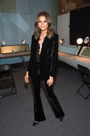 Zendaya Coleman opted for a black velvet pantsuit from her own line, given a sexy treatment with the addition of a plunging lace top, when she attended the 'Project Runway' fashion show.