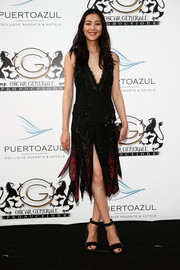 Liu Wen went for '20s-inspired sexiness in a beaded, deep-V black and red dress by Roberto Cavalli during the Puerto Azul Experience.