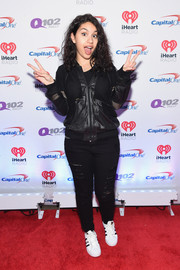 Alessia Cara posed in a black bomber jacket that she wore with ripped jeans and sneakers while on the red carpet at the Jingle Ball Show.