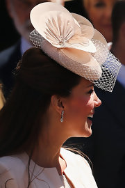 Kate Middleton matched her blush-pink coat with a lovely decorative hat of the same hue.