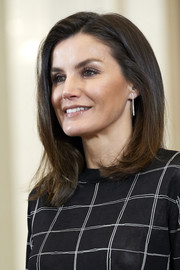 Queen Letizia teamed her 'do with a pair of dangling diamond earrings.
