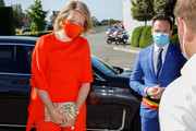 Queen Mathilde of Belgium styled her bright orange outfit with a graphic envelope clutch for her visit to the Gediflora Chrysanthemum nursery.