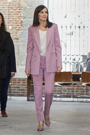 Queen Letizia of Spain kept it smart in a pink pantsuit by Hugo Boss while attending a meeting with APRAMP.