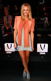 Lara wore a cheery orange suede jacket with strong shoulders and panels over a gray mini dress.