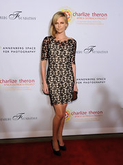 Charlize topped off her lacy frock with classic black patent leather pumps.