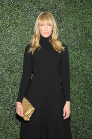 Toni Collette brightened up her outfit with a metallic gold Louis Vuitton Limelight clutch when she attended the screening of 'To Catch a Thief.'