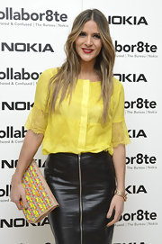 Amanda Byram was not afraid of color with this bright yellow loose blouse, which she paired with a dark leather skirt.