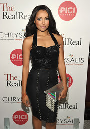 Kat Graham accessorized her spiked dress with a futuristic silver envelope clutch with chain details.