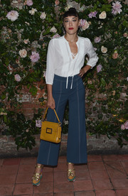 Mia Moretti added an extra splash of color with a mustard-hued purse.