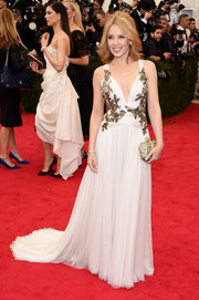 Kylie Minogue chose an elegant gold hard-case clutch to complement her gown.