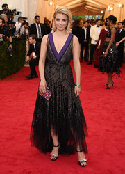 Dianna Agron went for edgy elegance at the Met Gala in a beaded black tulle gown by Miu Miu, featuring a deep-V purple neckline and a high-low hem.