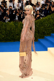 Kylie Jenner paired a gold box purse with a sexy see-through gown for the 2017 Met Gala.