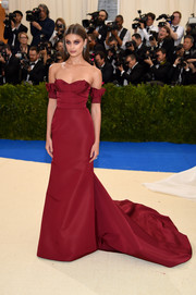 Taylor Hill looked breathtaking in a burgundy off-the-shoulder gown by Carolina Herrera at the 2017 Met Gala.