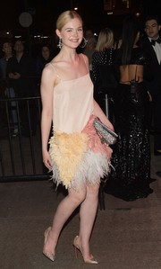 Elle Fanning channeled her inner flapper girl in a feather-embellished cocktail dress by Miu Miu for the Met Gala after-party.