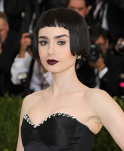 For her beauty look, Lily Collins went goth with dark red lipstick.