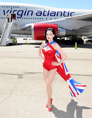 Dita wore a teeny-tiny red corset like only she can, while posing in front of a plane featuring her self portrait.