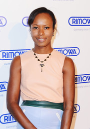 Shala Monroque styled her casual outfit with a fan pendant necklace when she attended the Rimowa NYC store opening.