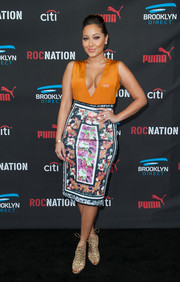 Adrienne Bailon looked vivacious at the Roc Nation pre-Grammy brunch in a figure-hugging, deep-V dress with an orange bodice and a floral skirt.