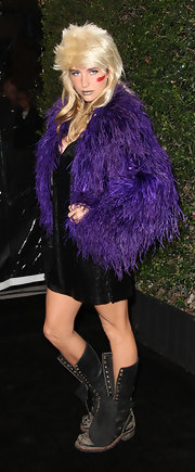 Kesha maintained her funky grunge aesthetic in battered and unlaced combat boots. A blond mullet and purple shag coat complete the quirky look.
