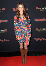 Nikki Reed topped off her print wrap dress with brown leather boots.