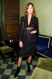 Alexa Chung was tough-chic in a grid-patterned tweed skirtsuit with brown leather trim and a lace-up midsection during the Rosetta Getty party.