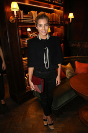 Adding more colors into the mix, Mollie King accessorized with a red, gray, and pink envelope clutch.