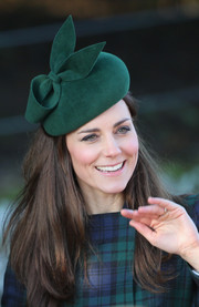 Kate Middleton matched her tartan coat with a bow-embellished green hat by Gina Foster for Christmas Day service.