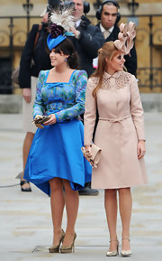 Princess Eugenie looked playful a the royal wedding in a blue Peter Pan inspired hat with a large flower and feathers.