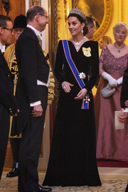 Kate Middleton looked downright regal in a black Alexander McQueen velvet gown with a V neck and pointy shoulders while attending a reception for the Diplomatic Corps.