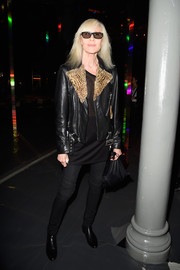 Betty Catroux attended the Saint Laurent fashion show wearing a black leather jacket with fur lapels.