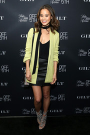 Jamie Chung layered a chartreuse cardigan over a black cami and a leather mini skirt for the opening of Saks OFF 5th's 57th street location.