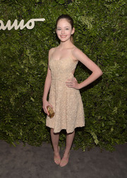 Mackenzie Foy paired her dress with an elegant gold tube clutch.