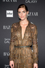 Hilary Rhoda attended the Harper's Bazaar Icons event wearing a beaded gold dress cinched with a skinny gray snakeskin belt.