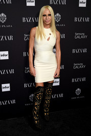 Donatella Versace styled her mini with a pair of patterned thigh-high boots.