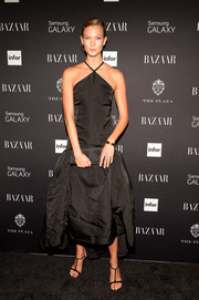 Karlie Kloss cut a shapely silhouette in a black drop-waist halter dress when she attended the Icons by Carine Roitfeld event.