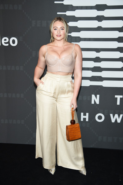 A camel-colored croc-embossed wristlet completed Iskra Lawrence's ensemble.