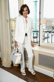 Ines de la Fressange looked pristine in a white pantsuit and a matching ruffle blouse at the Schiaparelli Couture show.