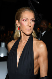 Celine Dion jazzed up her look with a red and gold tassel earring for the Schiaparelli Couture Fall 2019 show.