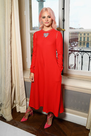 Pixie Lott brought a bold pop of color to the Schiaparelli Haute Couture show with this long-sleeve red midi dress from the label.