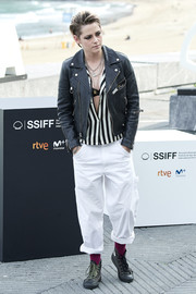 Kristen Stewart teamed baggy white slacks by Stan Ray with a striped shirt and a leather jacket for the 'Seberg' photocall at the 2019 San Sebastian Film Festival.
