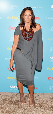 The designer donned a slate blue draped dress with a layered wooden statement necklace and flat sandals.
