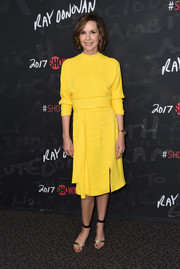 Embeth Davidtz completed her look with a pair of gold and black ankle-strap heels.