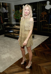 Sienna Miller matched her frock with elegant gold ankle-strap heels.