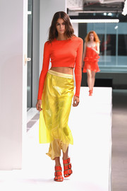 Kaia Gerber flashed her trim abs in a long-sleeve orange crop-top at the Sies Marjan runway show.