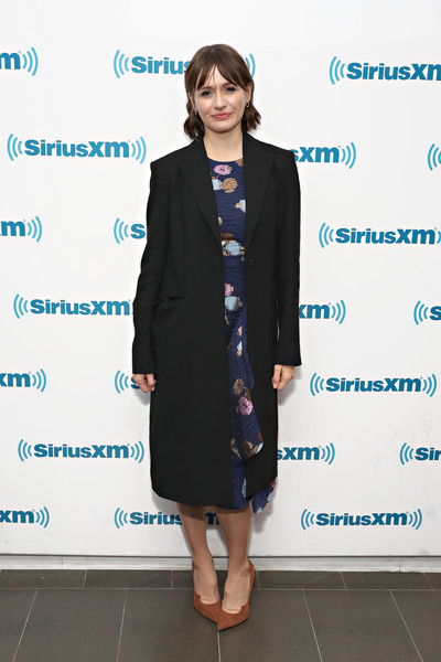 Emily Mortimer stopped by SiriusXM wearing a classic black coat over a floral dress.