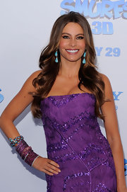 Sexy star Sofia Vergara paired her strapless purple gown with bright turquoise earrings and long and loose curls.
