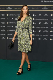 Irina Shayk teamed her dress with black ankle-strap platform sandals by Prada.