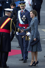 Queen Letizia of Spain paired a navy frame clutch with an embroidered skirt suit for the National Day Military Parade.