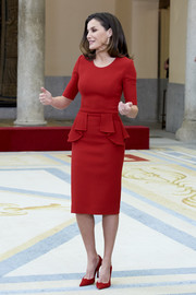 Queen Letizia matched her dress with a pair of red suede pumps by Magrit.