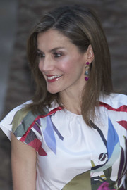 Queen Letizia of Spain matched her colorful dress with a pair of dangling multi-gem earrings for a dinner in Palma de Mallorca.